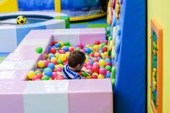 Happy boy having fun in ball pit in kids amusement park and indoor play center. Child playing with colorful balls in playground stock images