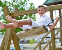 Happy boy having fun on a swing in a summer park. Stock Photos