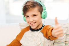 Happy boy in headphones showing thumbs up at home Stock Photos