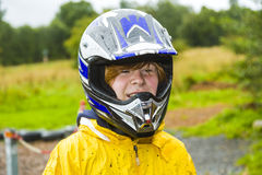 Happy boy with helmet at the kart trail. In rain with dirty face and clothing stock image