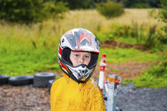 Happy boy with helmet at the kart trail. In rain with dirty face and clothing stock photos
