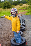 Happy boy with helmet at the kart trail. In rain with dirty face and clothing stock images