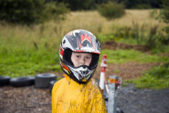 Happy boy with helmet at the kart trail. In rain with dirty face and clothing royalty free stock photography