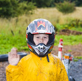 Happy boy with helmet at the kart trail. In rain with dirty face and clothing stock photo