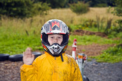Happy boy with helmet at the kart trail. In rain with dirty face and clothing royalty free stock photos
