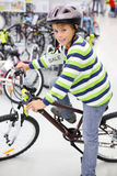 Happy boy in helmet sits on brown bicycle. And looks at camera in sports store Royalty Free Stock Photo