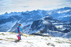 Happy boy with his baby sister in snow mountains Stock Photos