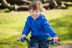 Happy Boy on his BIke in the Park Stock Images