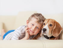 Happy boy with his dog lying on sofa Royalty Free Stock Image