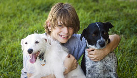 Happy Boy and his dogs. A smiling 12 year old boy holding his dogs in the grass Stock Photos