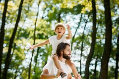 Happy boy with his father dressed in the white t-shirts walking in the park. Boy is sitting on the father`s shoulders stock photo