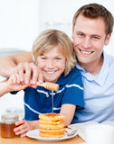 Happy boy and his father putting honey on waffles Stock Images
