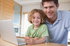 Happy boy and his father using a notebook Stock Photography