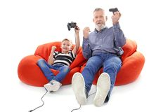 Happy boy and his grandfather with video game controllers Stock Image