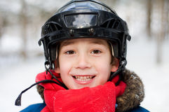 Happy boy in a hocky helmet. Closeup of a smiling six year old boy wearing a hockey helmet outdoors Stock Photography