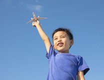 Happy boy holding a airplane toy with blue sky Stock Photos