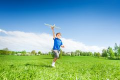 Happy boy holding airplane toy during running Royalty Free Stock Images