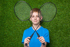 Happy boy holding badminton rackets over grass Stock Image