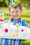 Happy boy holding cake at birthday party Stock Photography