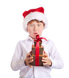 Happy boy holding christmas present wondering wat Royalty Free Stock Images