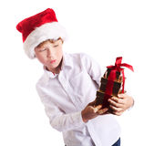 Happy boy holding christmas present wondering wat Stock Photos