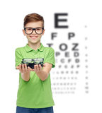 Happy boy holding eyeglasses over eye chart Royalty Free Stock Images