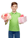 Happy boy holding flower bunch and gift box Stock Photos