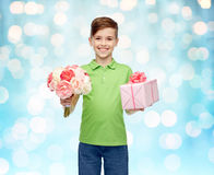 Happy boy holding flower bunch and gift box. Childhood, holidays, presents and people concept - happy boy holding flower bunch and gift box over blue lights Royalty Free Stock Photos