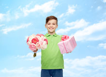 Happy boy holding flower bunch and gift box. Childhood, holidays, presents and people concept - happy boy holding flower bunch and gift box over blue sky and Stock Photo