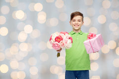 Happy boy holding flower bunch and gift box. Childhood, holidays, presents and people concept - happy boy holding flower bunch and gift box over lights Royalty Free Stock Photos