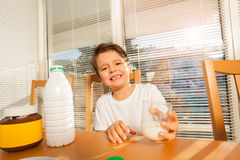 Happy boy holding glass with milk sitting at table Stock Photos