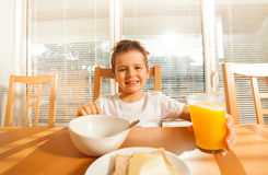 Happy boy holding glass with orange juice. Portrait of happy six years old boy sitting at a table and holding glass with orange juice in the kitchen Stock Image