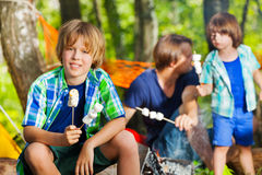 Happy boy holding grilled shmallows at campsite Royalty Free Stock Photos