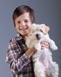 Happy boy holding his fluffy dog Stock Image