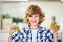 Happy boy holding kiwi. Happy boy holding a fresh kiwi in the kitchen Royalty Free Stock Photography