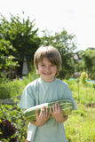 Happy Boy Holding Marrow In Garden Royalty Free Stock Photography