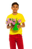 Happy boy holding pail with pink tulips. Happy boy in red jeans holding pail with pink tulips on the white background royalty free stock photos