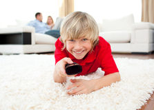 Happy boy holding a remote lying on the floor Royalty Free Stock Image
