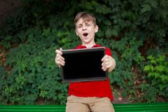 Happy boy holding tablet in hands. Education, electronic games addiction, childhood, family and people concept stock image
