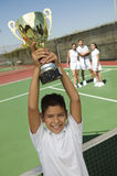 Happy Boy Holding Up Trophy On Tennis Court. Portrait of a boy holding Tennis up trophy at net with adults in the background on tennis court Royalty Free Stock Photo