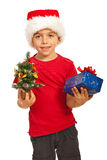 Happy boy holding Xmas tree and gift Stock Images