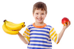 Happy boy holds a bananas and apple Royalty Free Stock Photo