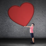 Happy boy holds big love symbol Stock Images