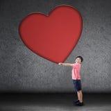 Happy boy holds big love symbol Stock Images