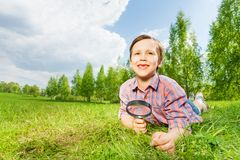 Happy boy holds magnifier lays on the green grass Stock Photo