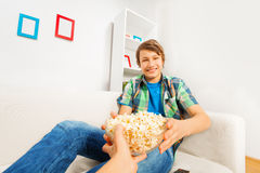 Happy boy holds popcorn bowl from someone's hand Stock Image