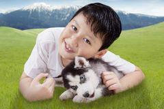 Happy boy and husky dog on meadow Stock Photography