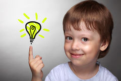 Happy boy with idea lamp. On grey background royalty free stock photo