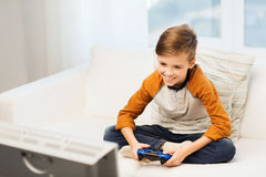 Happy boy with joystick playing video game at home Stock Images