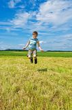 Happy boy jumping. On the green field Stock Photos